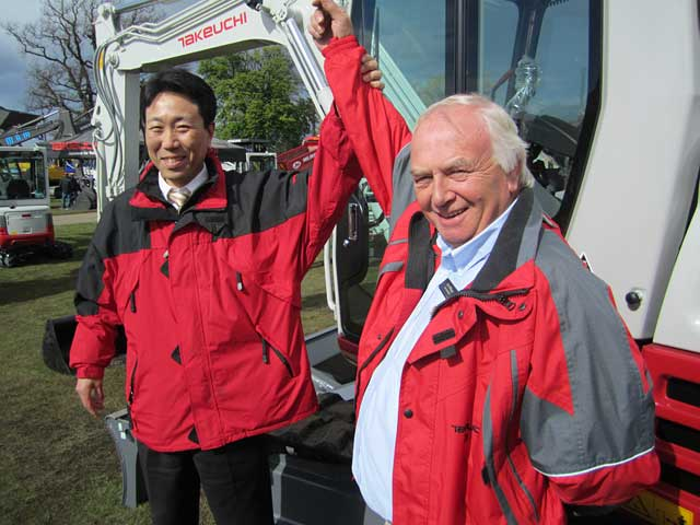 JUST CHAMPION: Jim Mulligan celebrates his award on the stand with Tomonori Tamaru, managing director of Takeuchi MFG (UK) Ltd.